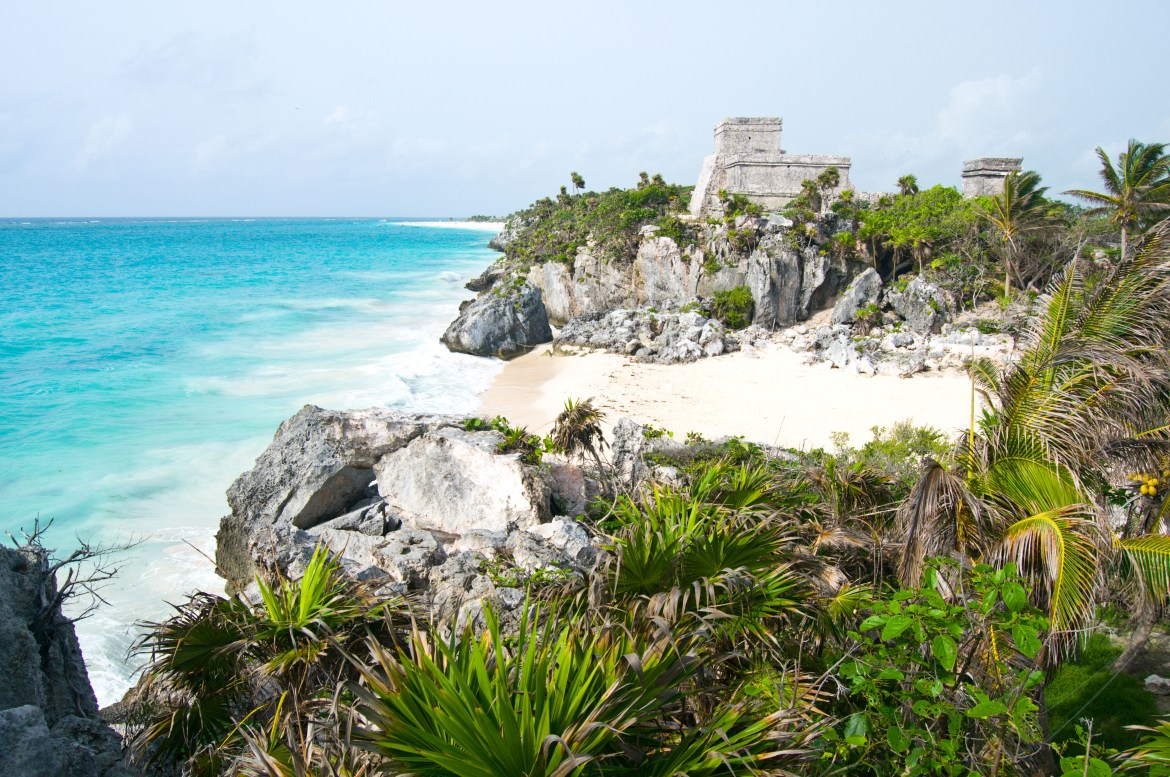 A view of the main stone structure at the Pre-Colombian Mayan ruins at Tulum, Yucatan Peninsula, Mexico. The stone structure sits on a cliff overlooking the turquoise-blue waters of the Caribbean Sea. A white sand beach, rock outcroppings, and dark green foliage fill the foreground.