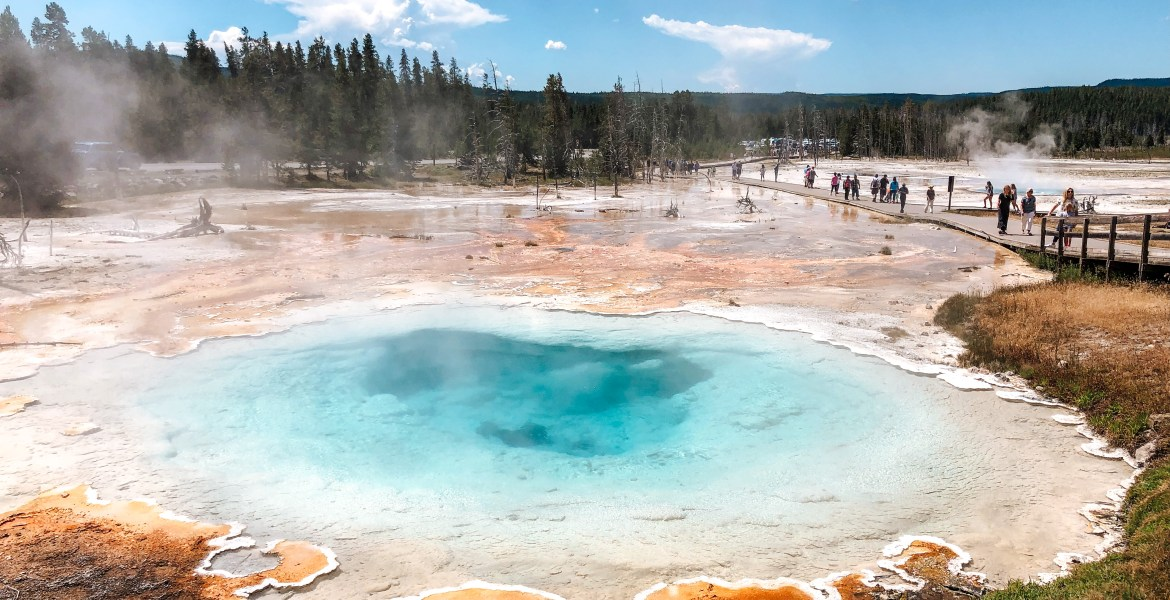 A large thermal spring connected to Celestine hot spring near Fountain Paint Pots in Yellowstone National Park, Wyoming. Deep blue sky contrasts with white clouds over the stark bacteria mats and mineral earth near the spring. The boiling water creates a deep blue and turquoise hue, surrounded by orange, yellow, and brown bacteria mats and a wide walkway for tourists to walk to viewing platforms.