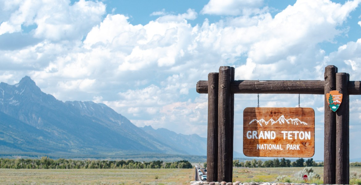 A view of the National Park Service sign at the entrance to Grand Teton National Park, Wyoming, just outside of Jackson, Wyoming. The Tetons sit beneath white clouds and a blue summer sky.