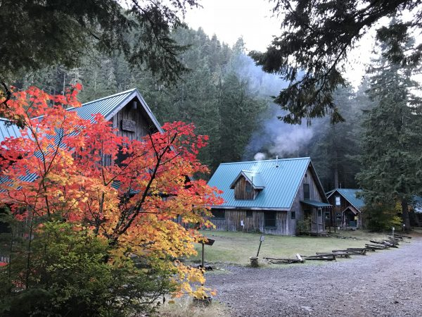 Oregon Life - Road Trips Oregon. The Ancient Forest Center at Opal Creek, Oregon, in the Opal Creek Wilderness. Historic cabins at Opal Creek can be reserved and rented. Changing fall leaves in the foreground contrast with the green tin roofs of the cabins, with smoke swirling above them at dusk in the mountains.