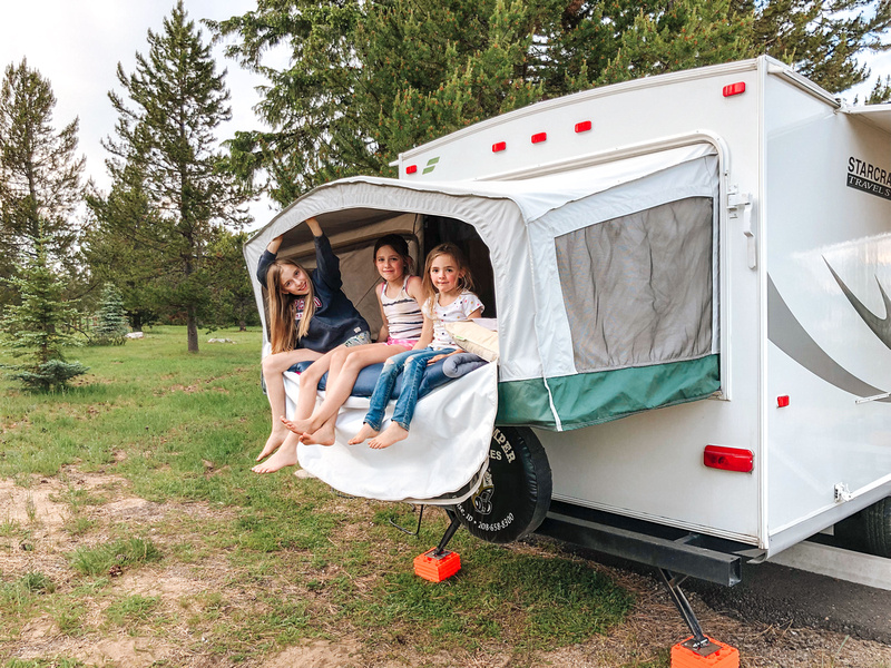 Active Recreation - Three girls sit in an open canvas tent trailer at Idaho's Lake Cascade State Park.
