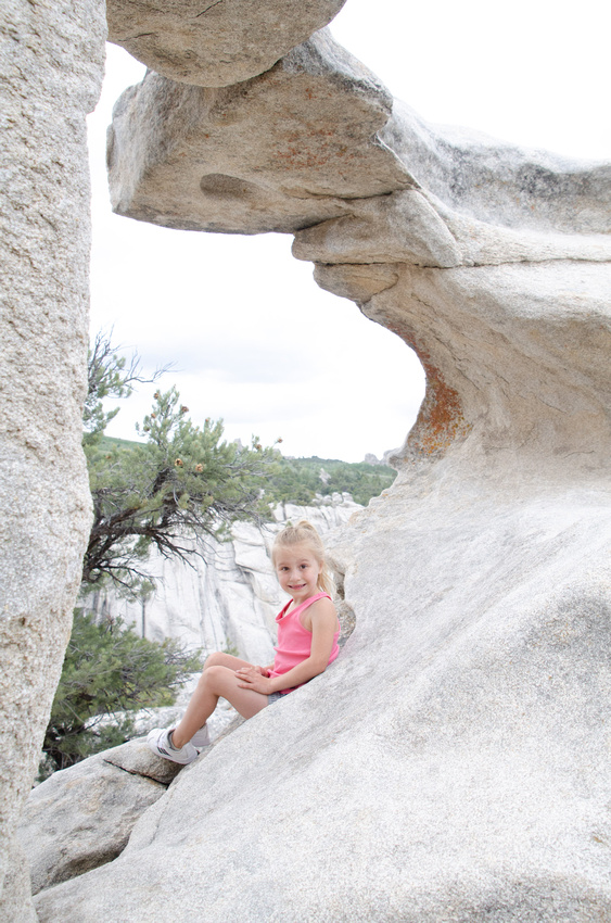 City of Rocks - Climbing Hiking Camping. A young girl sits beneath Picture Arch, in the center of City of Rocks National Reserve.