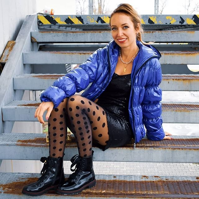 Modra bunda zena sedi na schodoch sekac second hand modny tucet