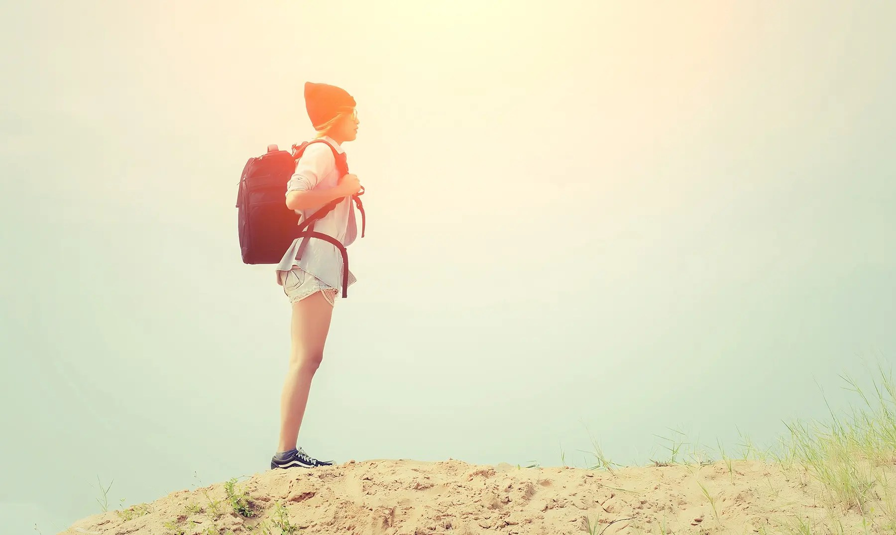 Teenage girl wearing glasses, carrying a backpack to the travel.