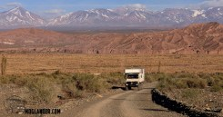 Andes mountains backdrop with Unimog Moglander climbing gravel road