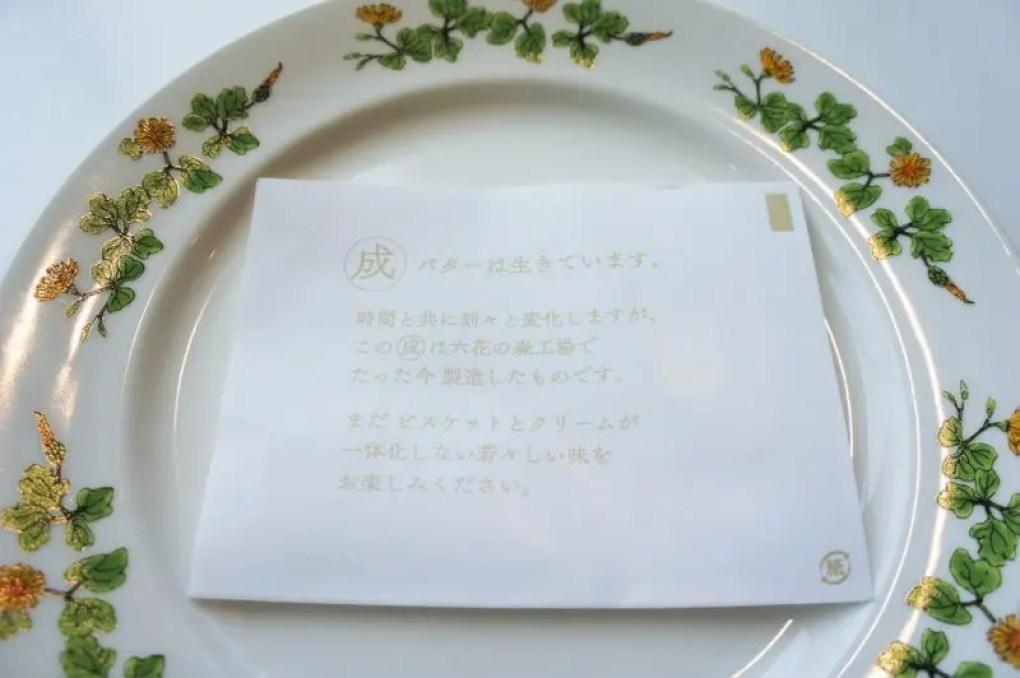 マルセイバターサンドの説明書をのせた皿が、テーブルに置かれている