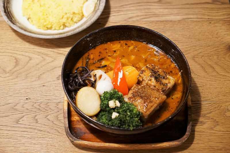 豚角煮と野菜が入ったスープカレーとライスがテーブルに置かれている
