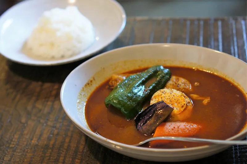 鶏肉と野菜、ゆで卵などが入ったスープカレーとごはんのお皿がテーブルに置かれいている