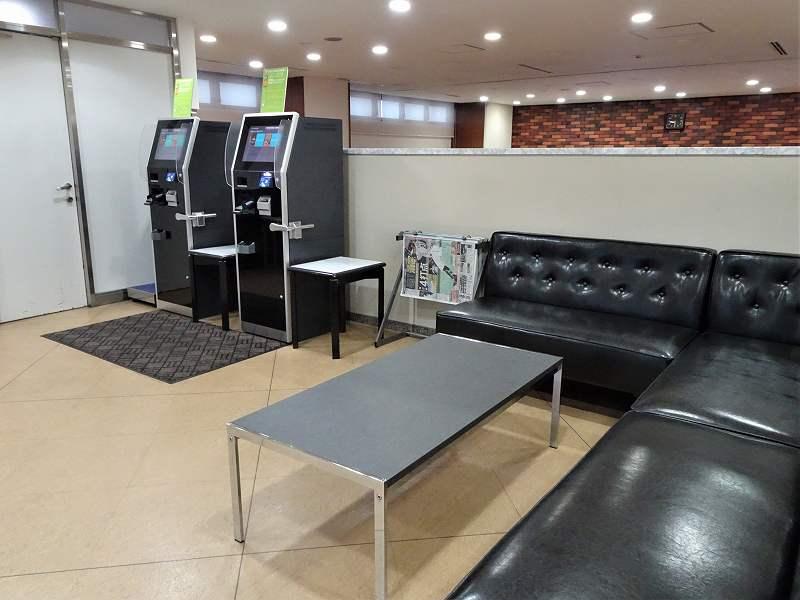 自動チェックイン機と革張りのソファ、テーブルが置かれている