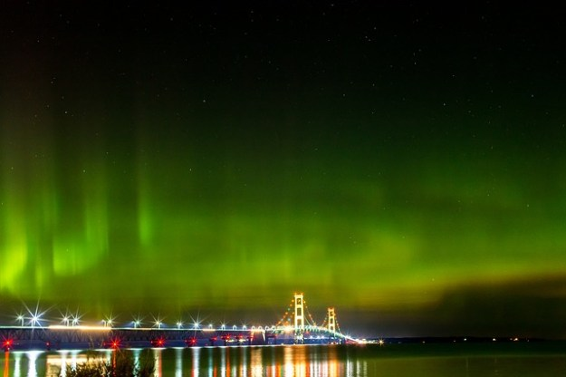 night scene of Michigan's Mackinac Bridge lit up with the background of green and orange swirls as if an aurora borealis were being displayed