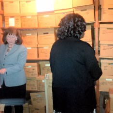 Mayor Ann Thane and Alderwoman Valerie Beekman look at boxes of records in City Hall's basement
