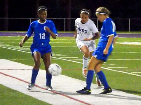 Ashley Searles kicks the ball past Naomi Frasier (#12) and Alex Wagner
