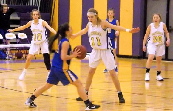 Sydney Hoefs (#10), Andie Gannon (#11), and Emily Schaufelberg (#20) on defense