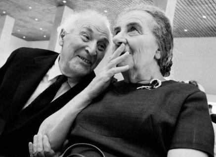 """Marc Chagall and Israeli PM Golda Meir. 'Marc Chagall's tapestries were hung in the Knesset with all due fanfare. The notables of Israel were waiting with bated breath for yet another masterpiece by the artist laureate of the east European Jewish ghetto to be revealed. I knew I could always come back and get a shot of the art. But not of the main figures. I turned around and refocused on Golda Meir sitting next to Chagall, just as the drapes dropped and The Gobelins were uncovered. """"What do you say to that, Golda?"""" Chagall said as he nudged her gently. """"Do you like it?""""'"""
