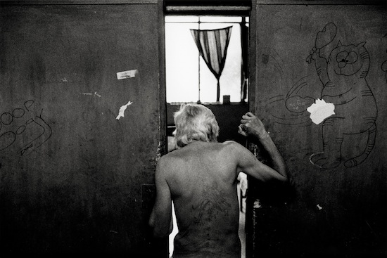 "Ian Martin: Hidden Minority: South Africa's White Poor-|Getty Images|- Hendrik ""Whitey"" Jacobus, 58, is a resident of an abandoned hospital in Vereeniging, South Africa. Here, he stands in the doorway of a room talking with another resident."