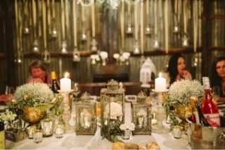 Vintage style lanterns with metal candlesticks and old gold urn planters were used as centerpieces on the main table