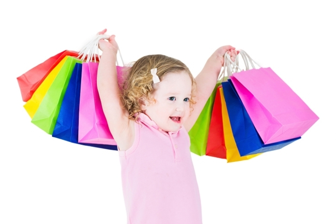 Cute little girl showing colorful shopping bags, isolated on white