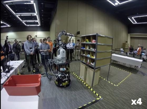 Ramię robota podjeżdża do półki, żeby uchwycić przedmiot