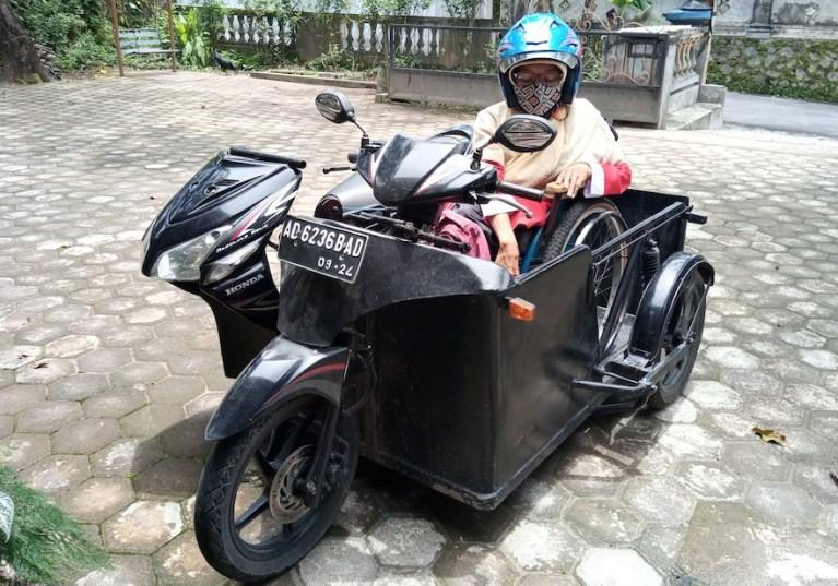 Bu Nani dengan motor yang sudah dimodifikasi untuk mempermudah aktivitasnya.