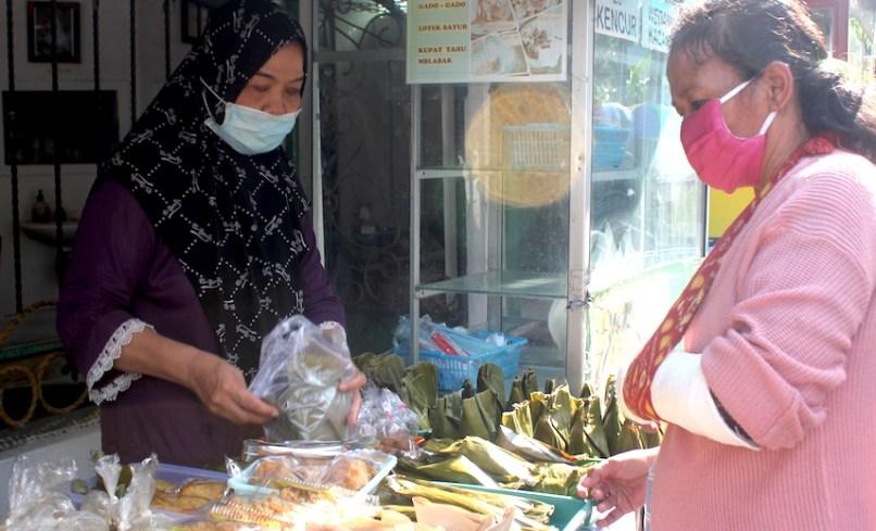 Salah seorang penjual takjil di Pasar Ramadhan Jogokariyan melayani pembeli. Foto oleh Brigitta Adelia/Mojok.co