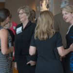 Women's Justice Award honorees and past recipients mingle at the cocktail reception before the awards ceremony. Judge Barbara Wallace, in striped dress, chats with retired judge Ann Covington. Cindy Parres Dillard and Mary Winter Doerhoff chat on right.