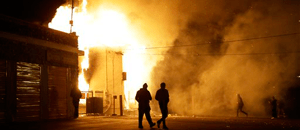 In this Nov. 24 file photo, people walk away from a storage facility on fire after the grand jury decision was announced in Ferguson. More than 700 National Guard troops were stationed preemptively throughout the St. Louis region. But Missouri Gov. Jay Nixon was inundated with criticism for not deploying the Guard outside businesses along a prominent Ferguson road where looting and arson had occurred after Michael Brown's Aug. 9 shooting. (AP Photo/Jeff Roberson, File)