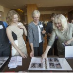 Women's Justice Award 2015 Woman of the Year, Virginia Fry, on right, comments on one of her pictures in the album of honorees at the reception desk at the Awards banquet Thursday night at the Four Seasons in St. Louis, MO.