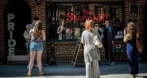 Visitors pose for photos outside the Stonewall Inn in New York. Fifty years ago, the Stonewall Inn was an underground gay bar where a police raid sparked a rebellion that fueled the modern LGBTQ rights movement. Today, it's still a bar, but a highly visible one. It's a landmark, and the patrons flocking in this week to honor the Stonewall riots' 50th anniversary include a gay police officers' group. AP Photo by Bebeto Matthews