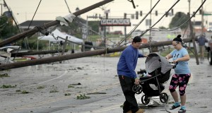 Jessica Rodgers and a neighbor Ray Arellana carry a stroller carrying Rodgers' sister Sophia Rodgers over downed power lines as they head to Rodgers' mother's apartment to check on damage Thursday, May 23, 2019, after a tornado tore though Jefferson City, Mo. late Wednesday. (AP Photo/Charlie Riedel)