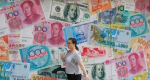 A woman walks by a money exchange shop decorated with different countries currency banknotes at Central, a business district in Hong Kong. China's yuan fell further Tuesday against the U.S. dollar, fueling fears about increasing global damage from Beijing's trade war with President Donald Trump. AP Photo by Kin Cheung