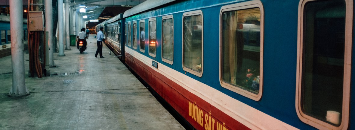 blue, white, and red night train parked at concrete platform. Passengers wait nearby.