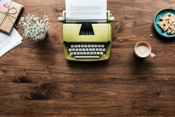 green typewriter, flowers, wrapped gift, plate of chocolate chip cookies, mug of coffee on a wooden table