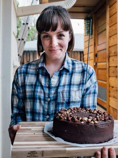 mollie wears a blue plaid button-down and holds a chocolate layer cake topped with hazelnuts on a wooden cutting board