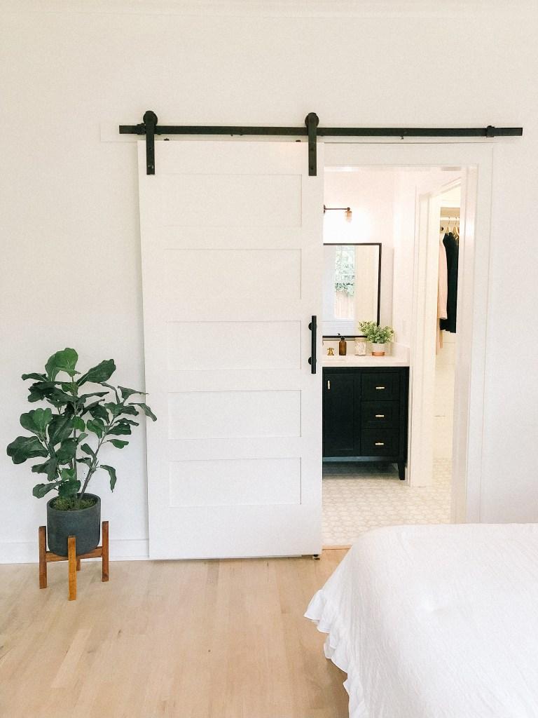 white bedroom sliding barn door master bathroom suite | 102-year-old fixer upper house renovation | mid century modern Scandinavian home design | house flip reno