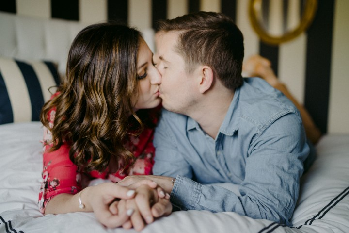 photo of couple kissing on the bed