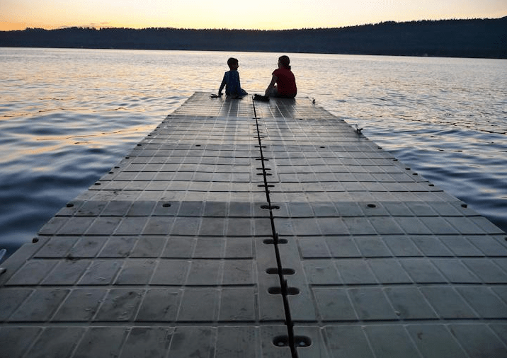 Two children sitting on a dock