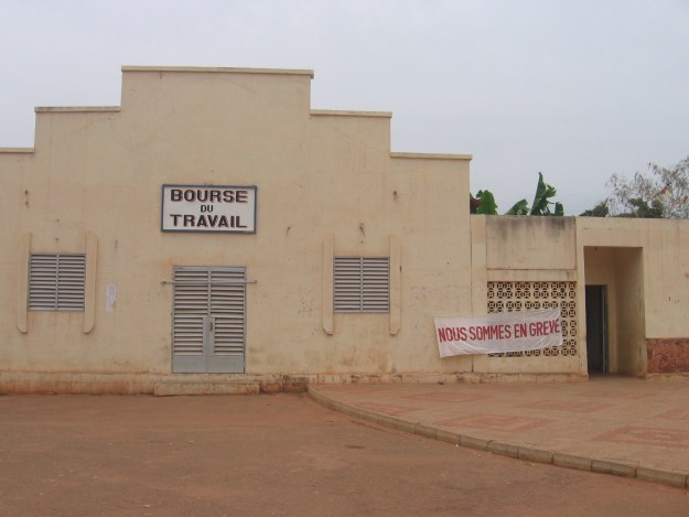 "Image of the Bourse du Travail in Bobo-Dioulasso shuttered, with a banner out front announcing ""Nous sommes en grève"""
