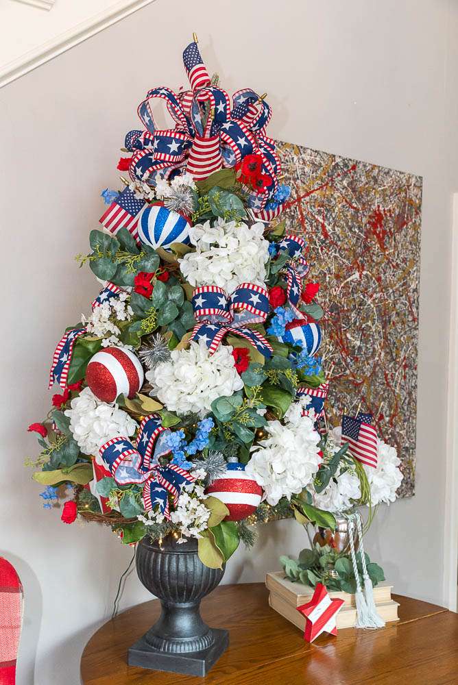 A 4th of July Christmas tree decorated with bow picks and hydrangeas.