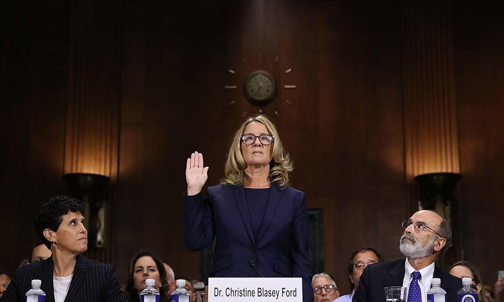 Christine Blasey Ford testifies in Washington, DC, as lawyers Debra Katz and Michael Bromwich look on.