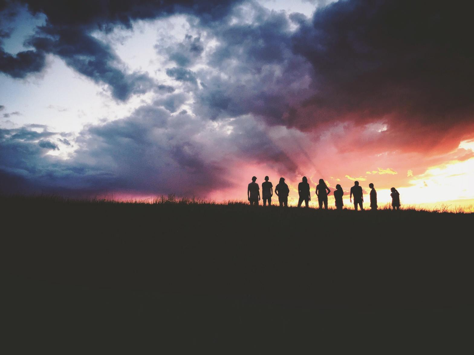 silhouetted people in front of colorful sky
