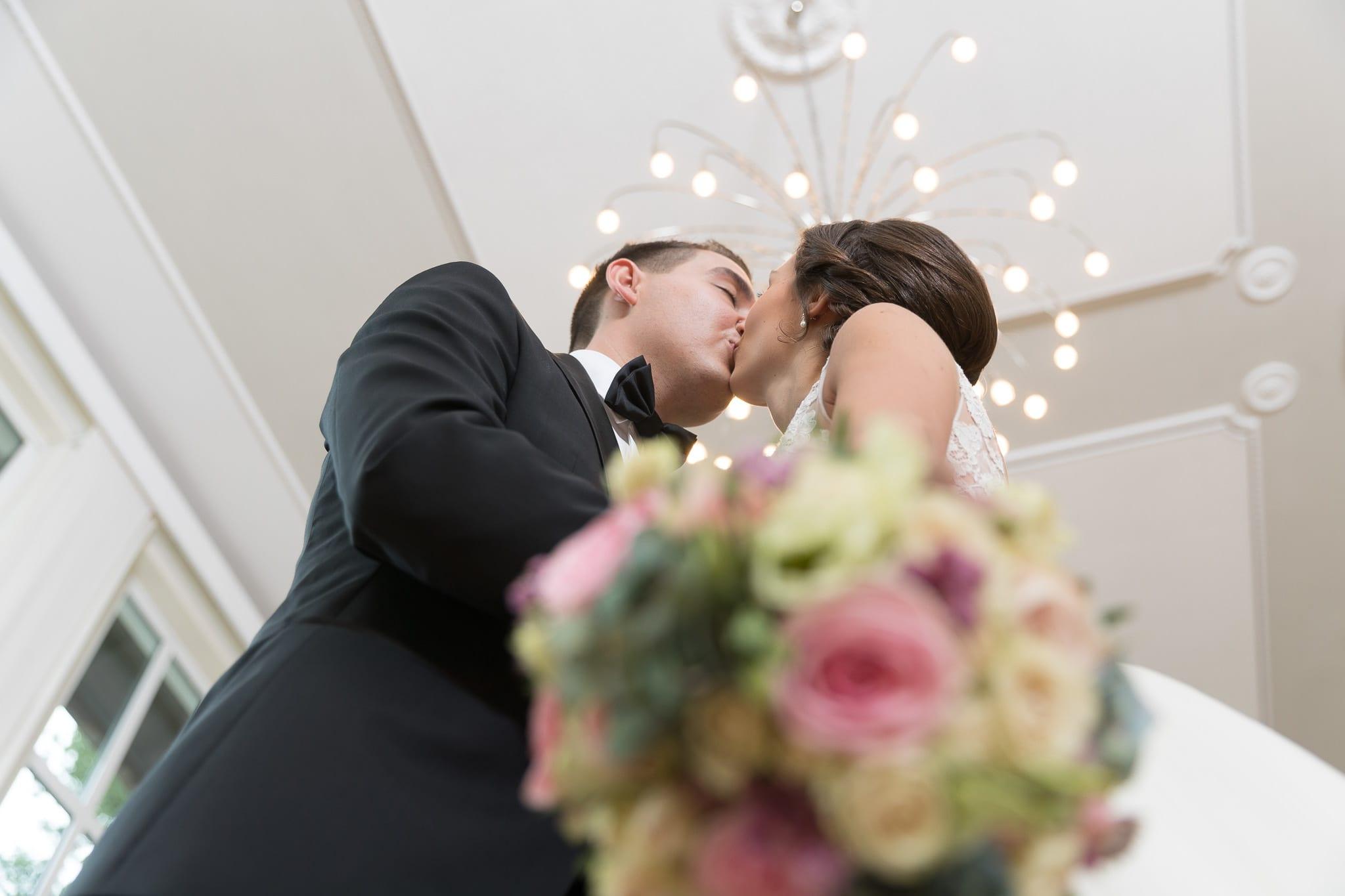 Brautpaar Kuss mit Blumenstrauss