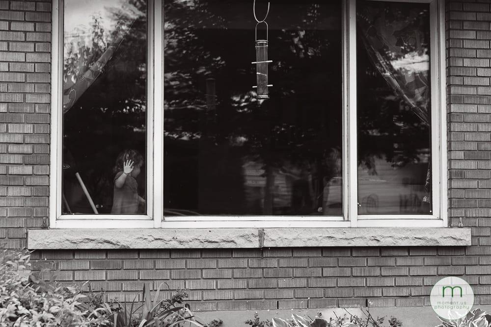 girl with hand on window