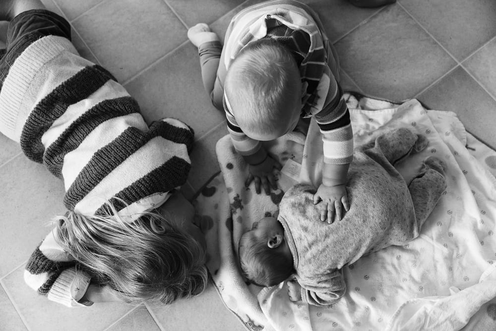 Cornwall family photographer - sisters on kitchen floor with newborn