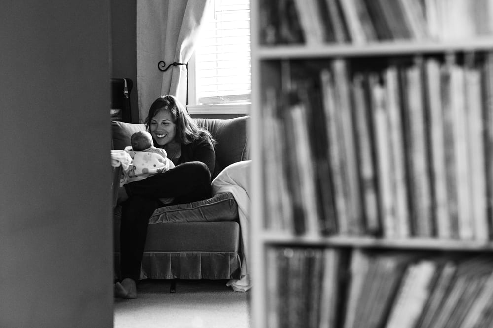 Cornwall family photographer - mom with baby in armchair