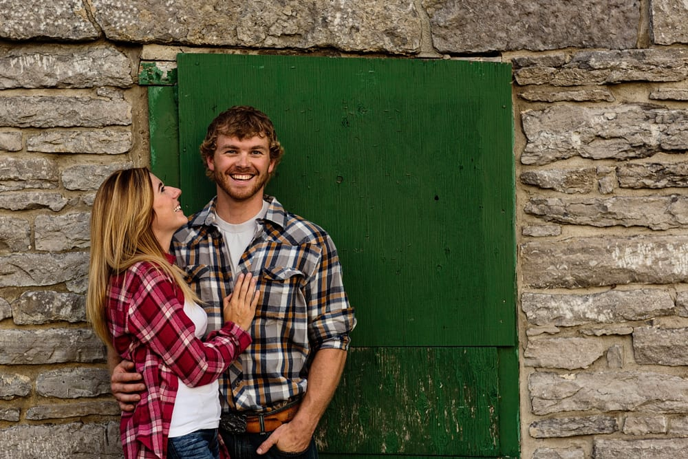 Ontario wedding photographer - couple cuddling for Cornwall engagement photos in front of green door
