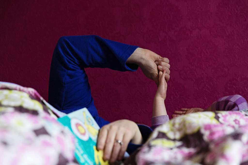 mom holding daughter's hand in bed