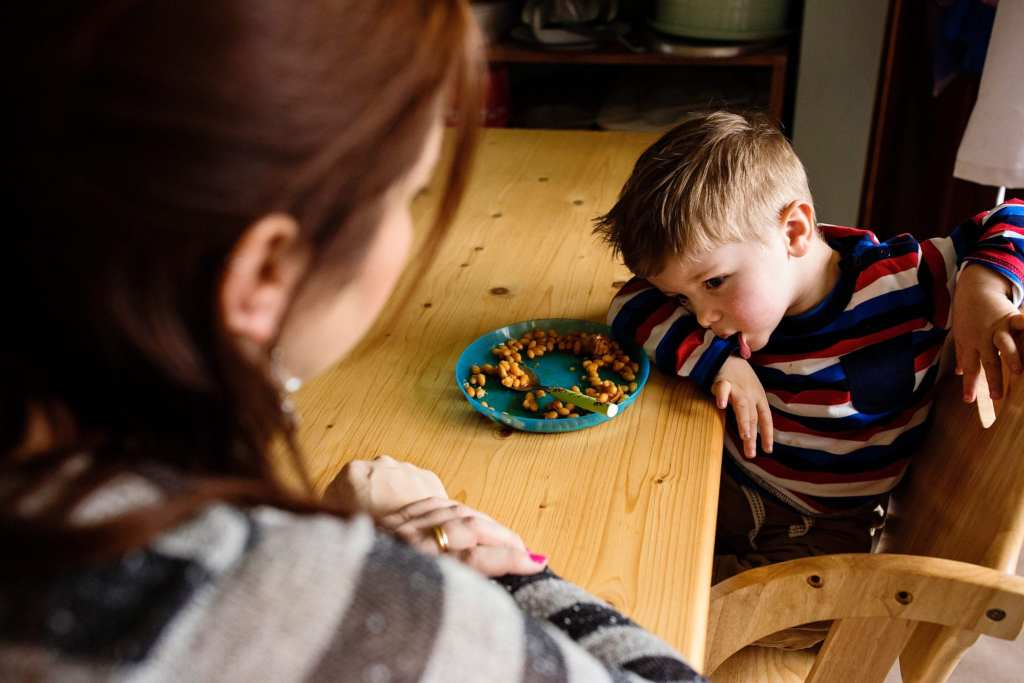 boy looking torn about food choice during South Wales family session