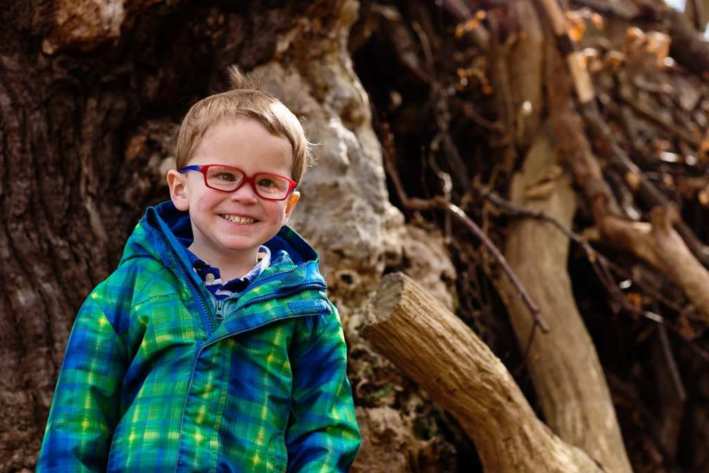 Boy smiling on tree during London family photography session