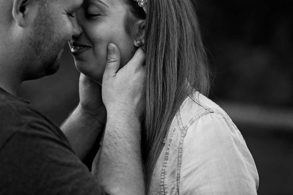 man leans in close to fiancee during St Raphael's engagement session