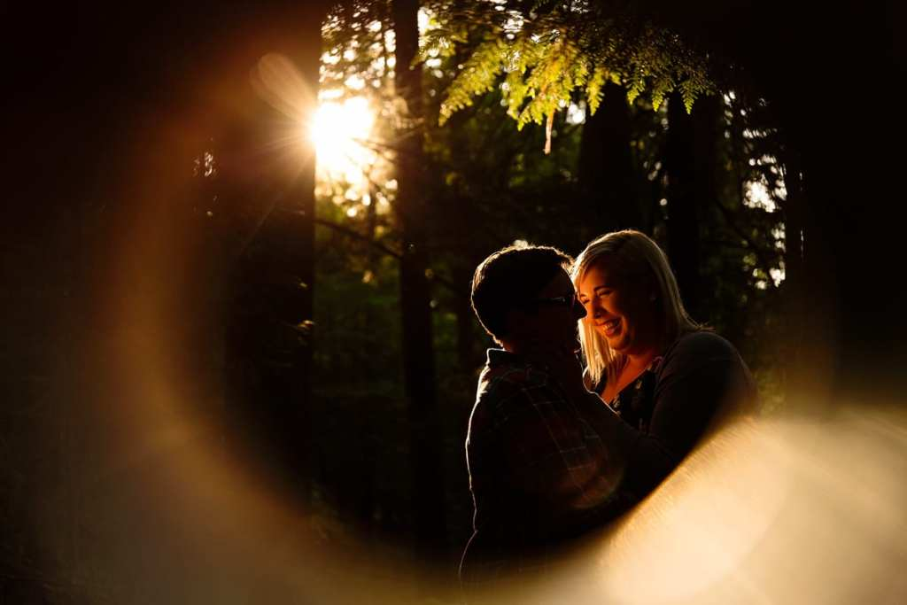 Girl holding fiance's face in woods